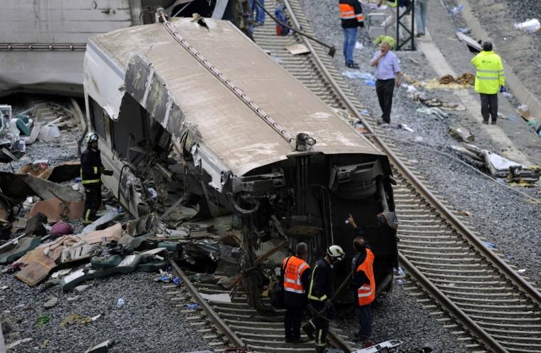 Спасатели осматривают обломки крушения поезда близ Сантьяго-де-Компостела, северо-западе Испании, в начале 25 июля 2013.  Поезд сошел с рельсов за пределами древних северо-западной испанском городе Сантьяго-де-Компостела в среду вечером, погибли по меньшей мере 77 человек и ранено до 131 в одном из худших бедствий Европы железной дороге.  (Eloy Alonso / Reuters фото)