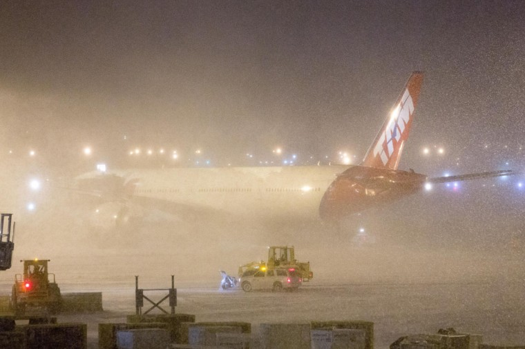 A TAM airlines plane sits shrouded by snow as plows work around it at John F. Kennedy International Airport in New York January 21, 2014. A winter storm packing snow and Arctic cold slammed the northeastern United States on Tuesday, grounding 3,000 flights, shutting down governments and schools and making travel a potential nightmare for millions. (REUTERS/Andrew Kelly)