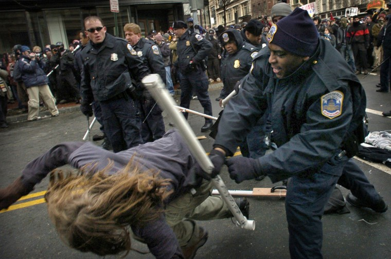 Washington, D.C. - 2005 - Washington Metropolitan police violently subdue a large group of young protesters, linked to the Anarchist movement, as the protesters attempted to storm a barricade at 7th and D Streets during the second inaugural of George W. Bush. The police are wielding PVC tubes taken from the protesters' banner, which was destroyed at the start of the melee. The police also used pepper spray to push the protesters back from the intersection. (Amy Davis / Baltimore Sun Staff)
