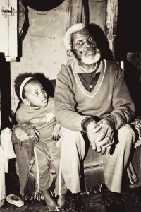 black and white rural grandfather and granddaughter in a shack - 2 people, people sitting and beard