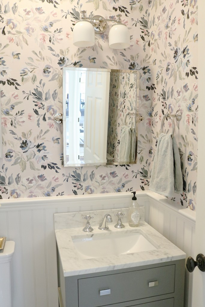 I am so excited to reveal our Powder Bathroom Makeover!  The before and after transformation is amazing!  We used Thassos mosaic Marble tile, Caitlin Wilson Design Wallpaper, Wayfair bathroom vanity, Pottery Barn bathroom fixtures. The Powder bathroom makeover has a modern, farmhouse but elegant style with navy and gray accents. || Darling Darleen #darlingdarleen #powderbathroom #mosaictile