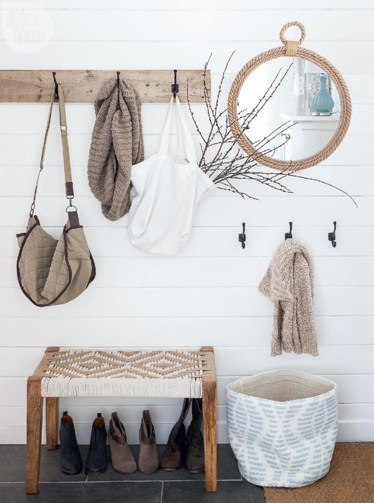 A wall with hooks hung at various heights provide storage solutions in an entryway