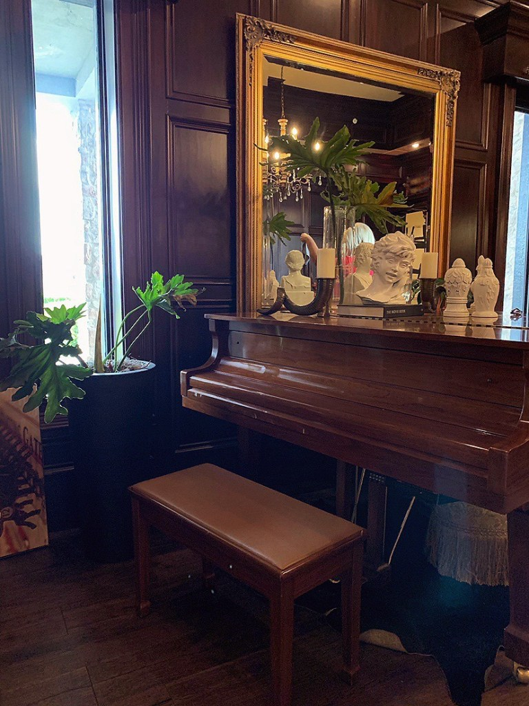 Photo of a piano in a den with wood-lined walls.