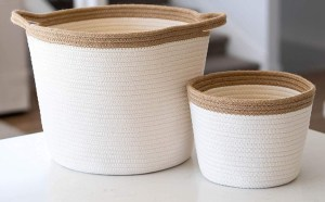 2 white and brown jute baskets sit on a counter.