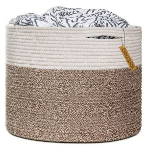 a large white and brown basket with a blanket overflowing the top