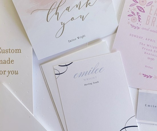 An assortment of custom stationery including invitations, thank you card, and business card.