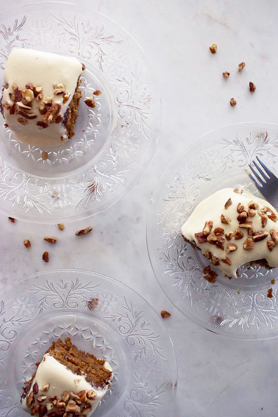 Three crystal plates holding slices of cake with frosting and pecans sit on a marble table.