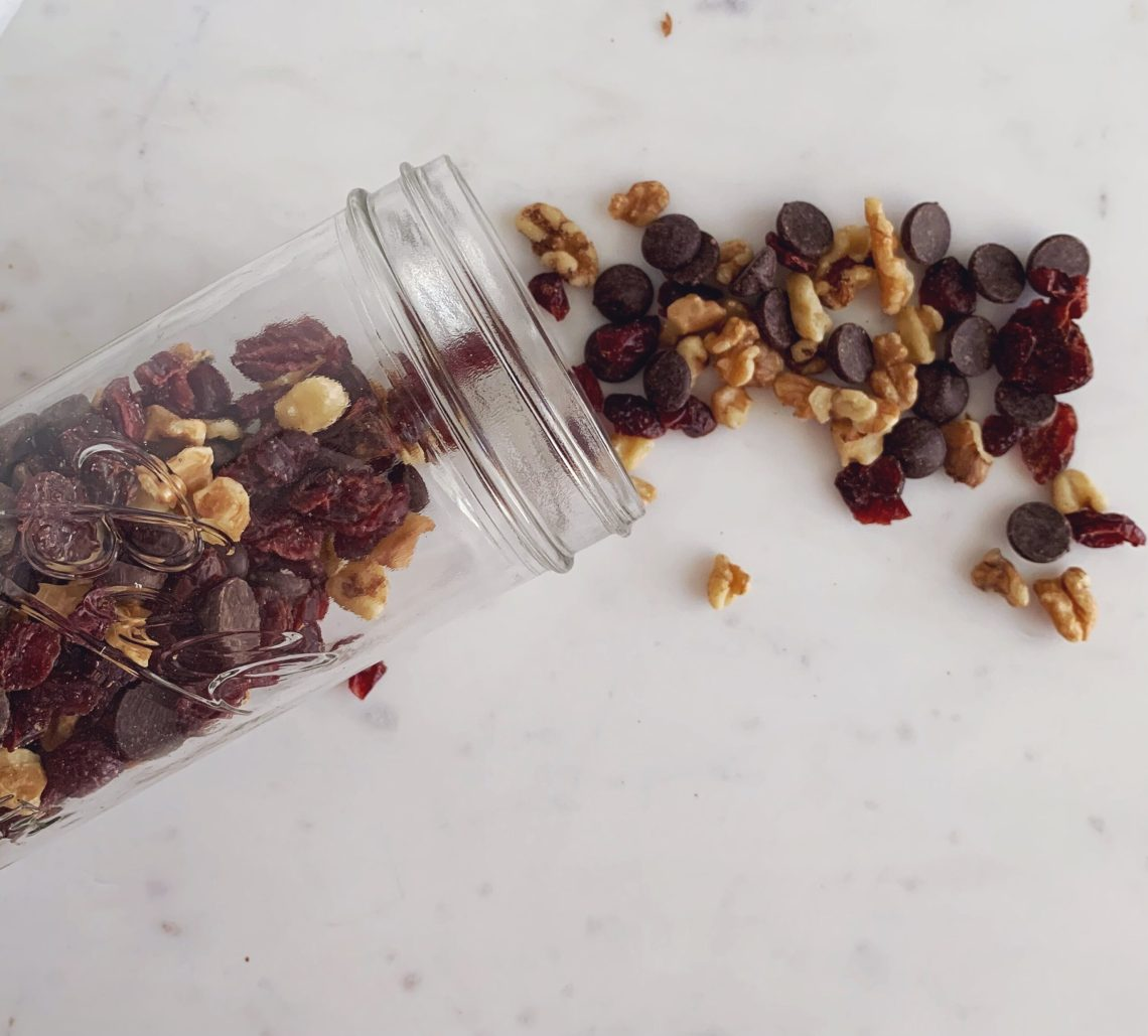 A jar lays on a table with a cranberry, walnut, and chocolate snack mix spilling out.