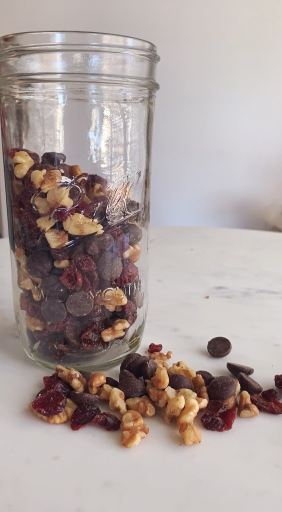 A jar sits on a table and is filled with a cranberry, walnut, and chocolate snack mix.