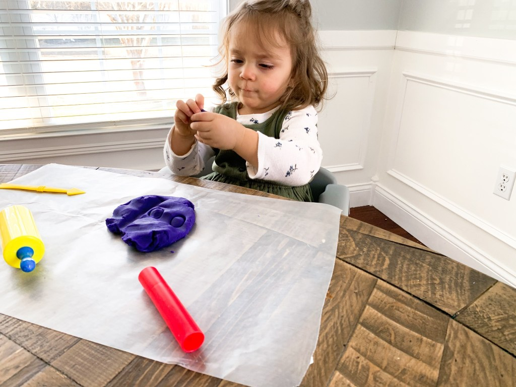 A toddler plays with homemade playdough while seated at a table.