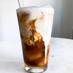 A glass of iced coffee with heavy cream swirling throughout.