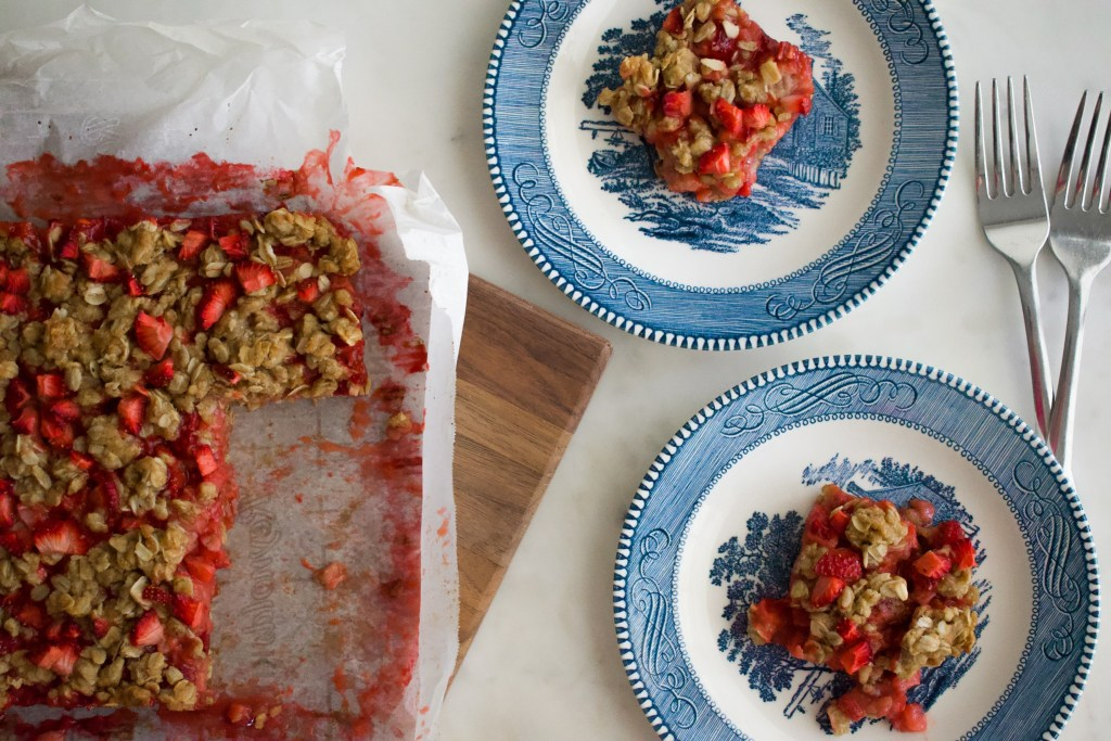 A baking pan of strawberry crumble bars with chopped strawberries sprinkled over the top sits next to two plates with slices of crumble bars.