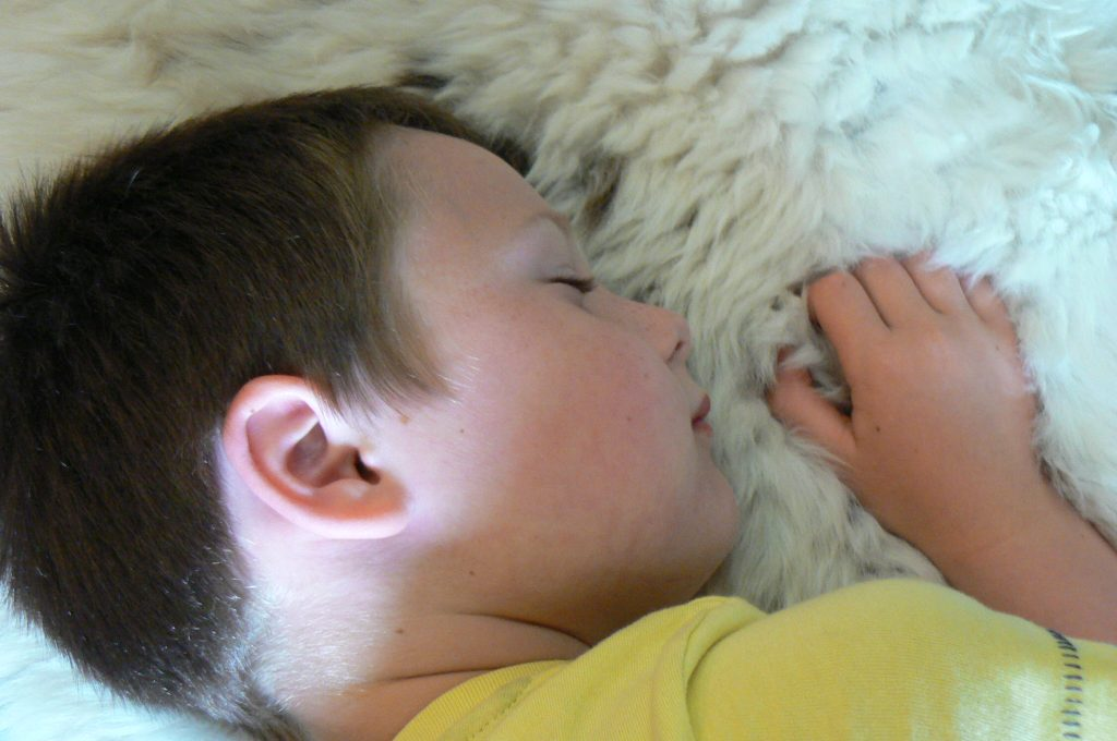 Child sleeping on sheepskin