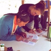 Promotora Santusa checks children's vaccine cards during a vitamin campaign in the community of Huilloc