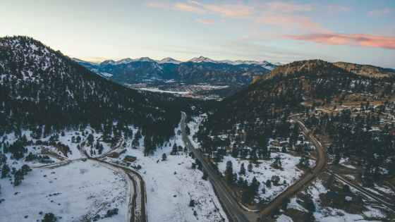 aerial view of road between trees and mountains