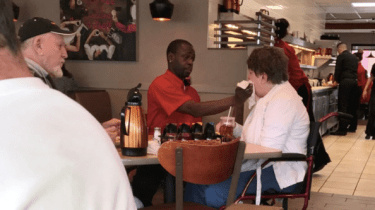 IHOP waiter Joe Thomas is getting attention from around the world after a photo of him helping a customer eat her meal went viral.