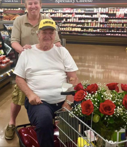 Gregory R. Johnson takes time to speak with a stranger, an elderly widower who is buying flowers and cake to commemorate his late wife's birthday.