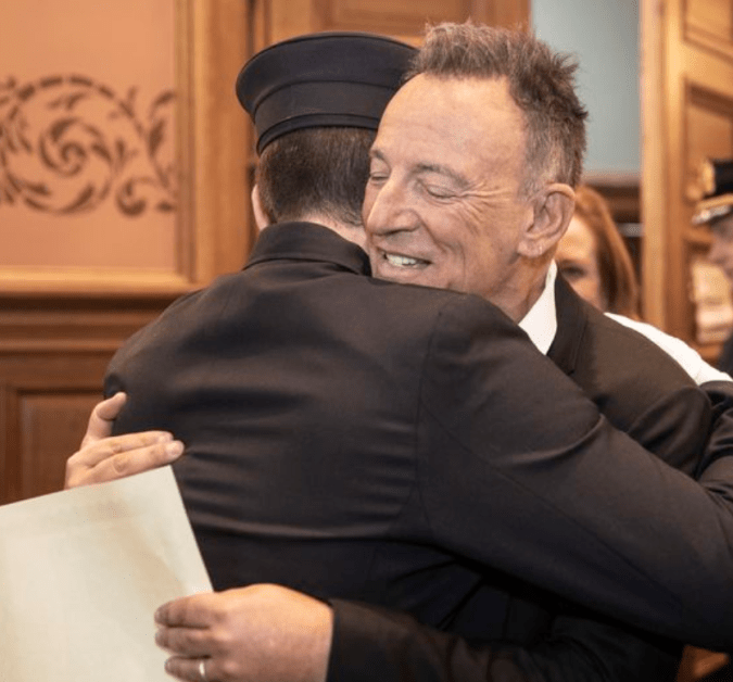 Bruce Springsteen hugs his youngest son, Sam, as he's sworn in as a Jersey City firefighter.