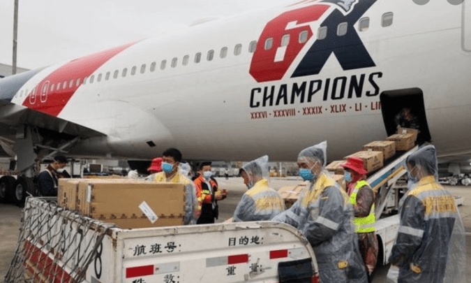 Workers in protective gear load up more than a million N95 masks onto the New England Patriots team plane in Shenzhen, China.