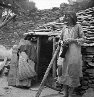 """Φτώχεια ελεεινή, μα και νοικοκυροσύνη -η αξιοπρέπεια της ελληνίδας μάνας. Γυναίκα έξω από το """"σπίτι"""" της στα Κανάλια Μαγνησίας το 1946 (φωτογραφία της Βούλας Παπαϊωάννου)"""