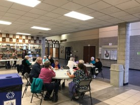 Older adults at tables in PAC lobby