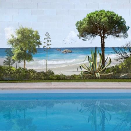 Mural con paisaje de playa pintado a mano en pared exterior de patio con jardín y piscina
