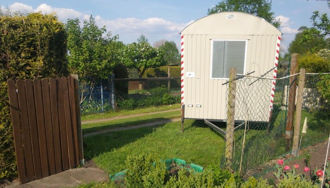 Grauer Bauwagen bei der Anruft am Garten. Der Zaun musste versetzt werden, um den Bauwagen in den Garten zu bekommen.