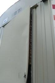 Das Blatt der Tür im Bauwagen wurde angehebelt und man sieht die Pappverkleidung im Inneren.