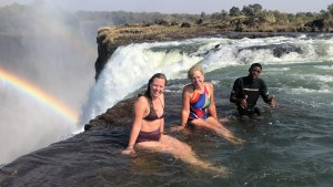 three people sitting on rock edge of waterfall