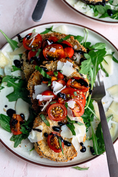 Crispy air fryer eggplant Milanese on a bed of arugula, with cherry tomatoes tossed in balsamic vinegar, basil, shaved parmesan and balsamic glaze!Air Fryer Eggplant Milanese - Dash Of Mandi