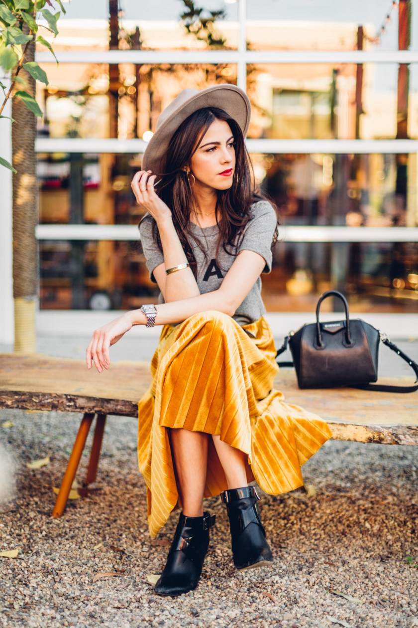Jackie Roque styling a velvet pleated skirt, Sol Angeles Ciao Tee and a Givenchy Micro Antigona Bag in Malibu.