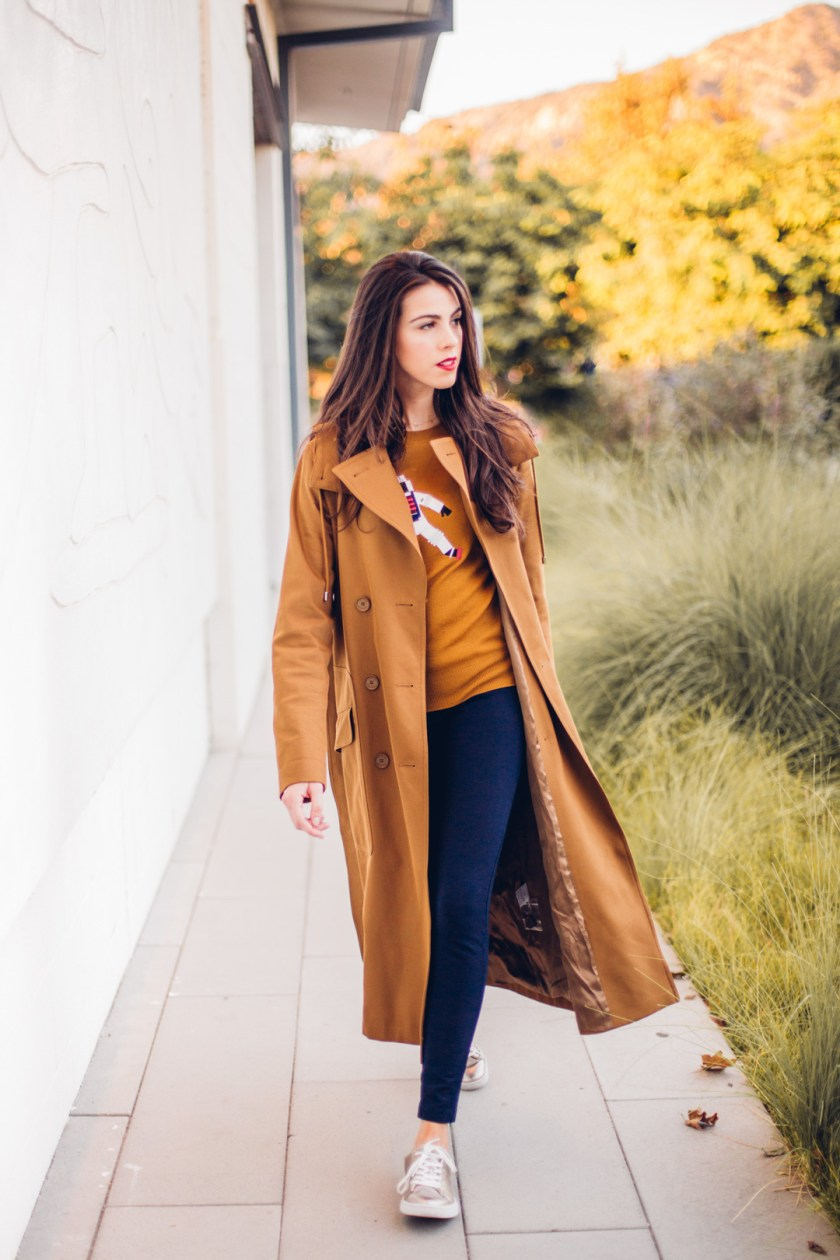 Jackie Roque styling a Lacoste Fall 2017 look with a brown trench coat and astronaut sweater in Malibu.