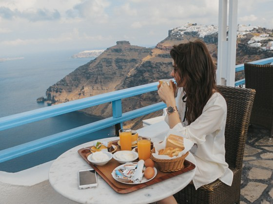 dasynka-fashion-blog-blogger-influencer-inspiration-shooting-model-globettrotter-travel-girl-lookbook-instagram-long-hair-street-style-casual-italy-lifestyle-outfit-poses-santorini-greek-greece-island-caldera-fira-oia-arkotiri-blue-domes-off-shoulder-blouse-shorts-white-louis-vuitton-pochette-hermes-bracelet-forever21-backpack-asos-hat-big-inspo-look
