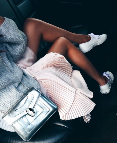 Girl with grey sweater, pink plated skirt, Bvlgari silver bag and white sneakers.