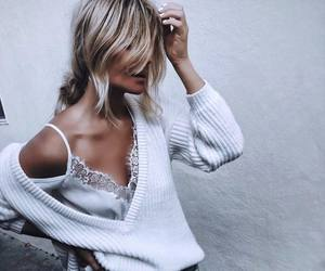 Image -blonde girl wearing white silky lace top and white woollen sweater
