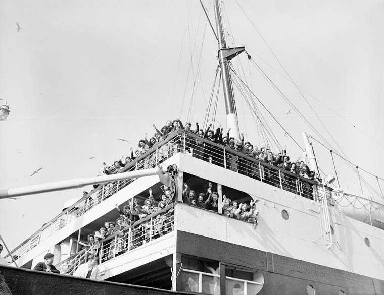 War brides, en route to Canada aboard S.S. Letitia, waving goodbye to families and friends.