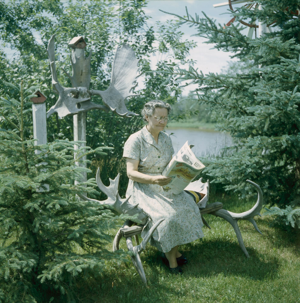 older woman reading the paper 1956 canada surrounded in antlers