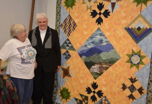 At the Personal Enrichment Open House, VGCC Quilting student Paulette Graham (left) and her instructor, Peggy Stocks of Kerr Lake, enjoy a quilt that Graham made for a competition held in conjunction with the 75th anniversary of Great Smoky Mountains National Park. Graham drives all the way from Raleigh to Henderson to take the quilting class. (VGCC photo)