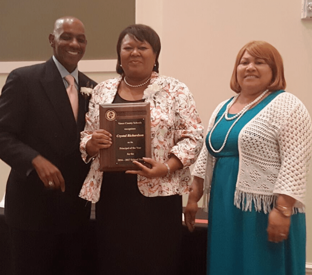 Crystal Richardson of Clarke Elementary School, center, accepts the 2016-2017 VCS Principal of the Year plaque from Jackson and White.