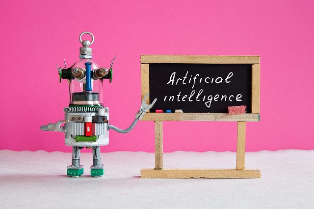Image of robot pointing to blackboard saying artificial intelligence