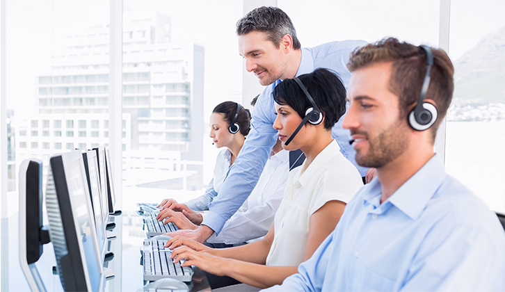 Picture of a gentleman consulting contact center employees. Services offered by DataTel Communications of Idaho.