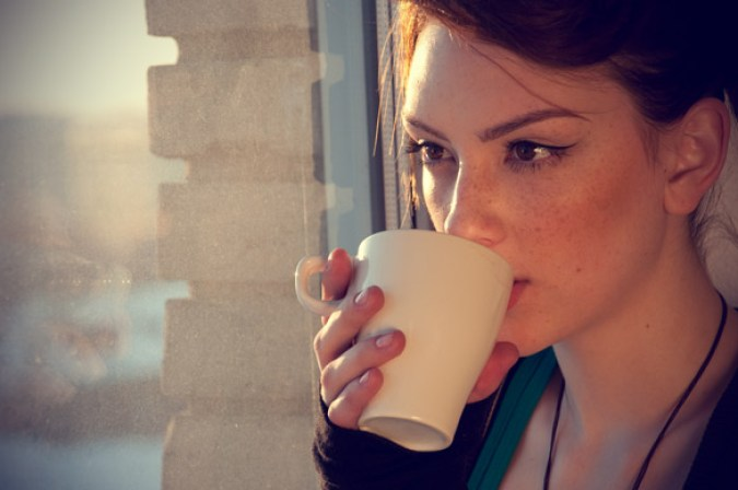 Beautiful-young-woman-in-casual-wear-dreaming-with-cup-of-hot-tea-over-window.jpg