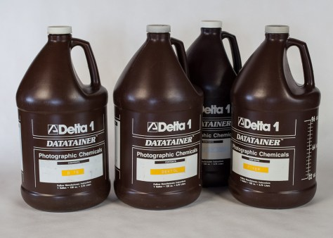 Four one-gallon Delta 1 plastic photographic chemical bottles.