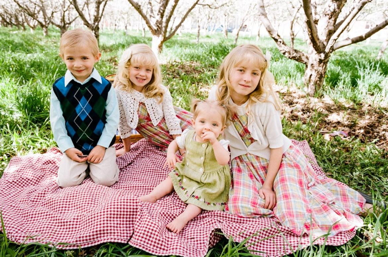 children sit in an orchard