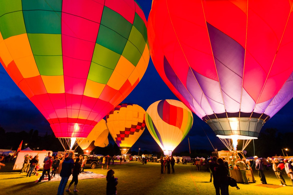 People tour the hot air balloons at night