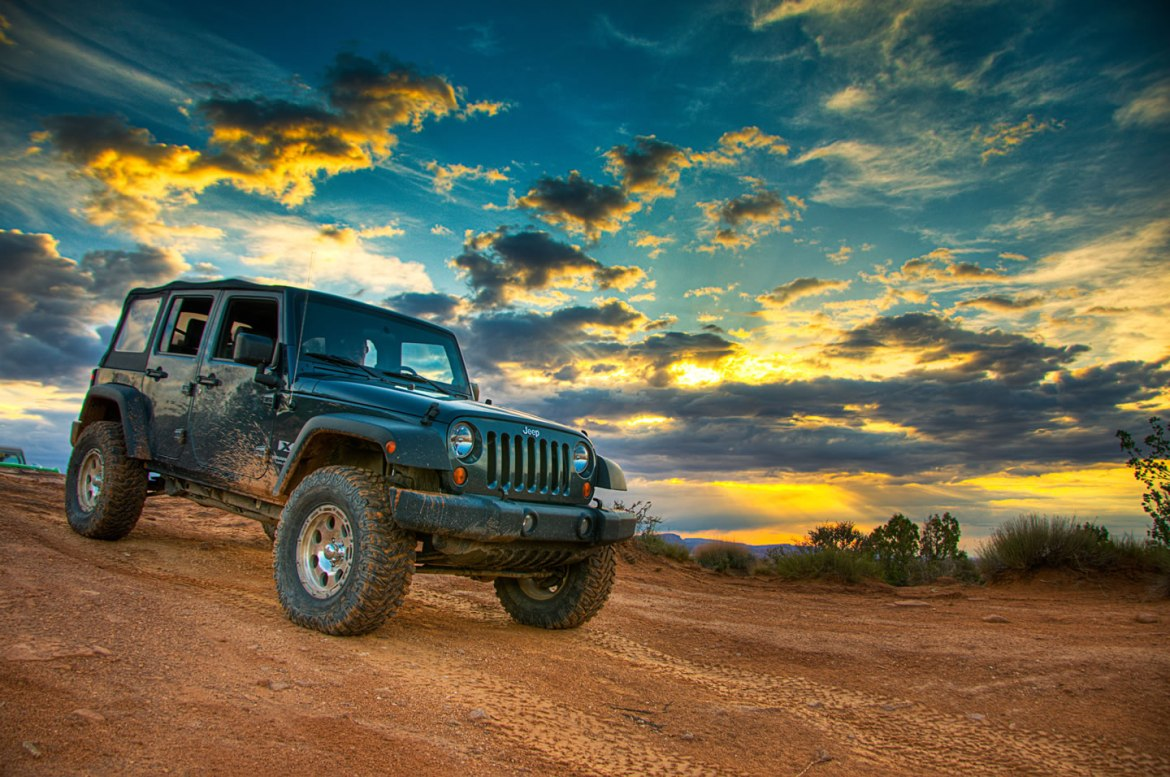 A Jeep Wrangler watches the sunset over Moab