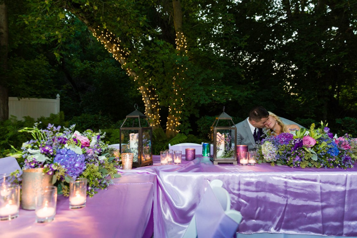 Bride and groom kiss during a quite moment at the reception
