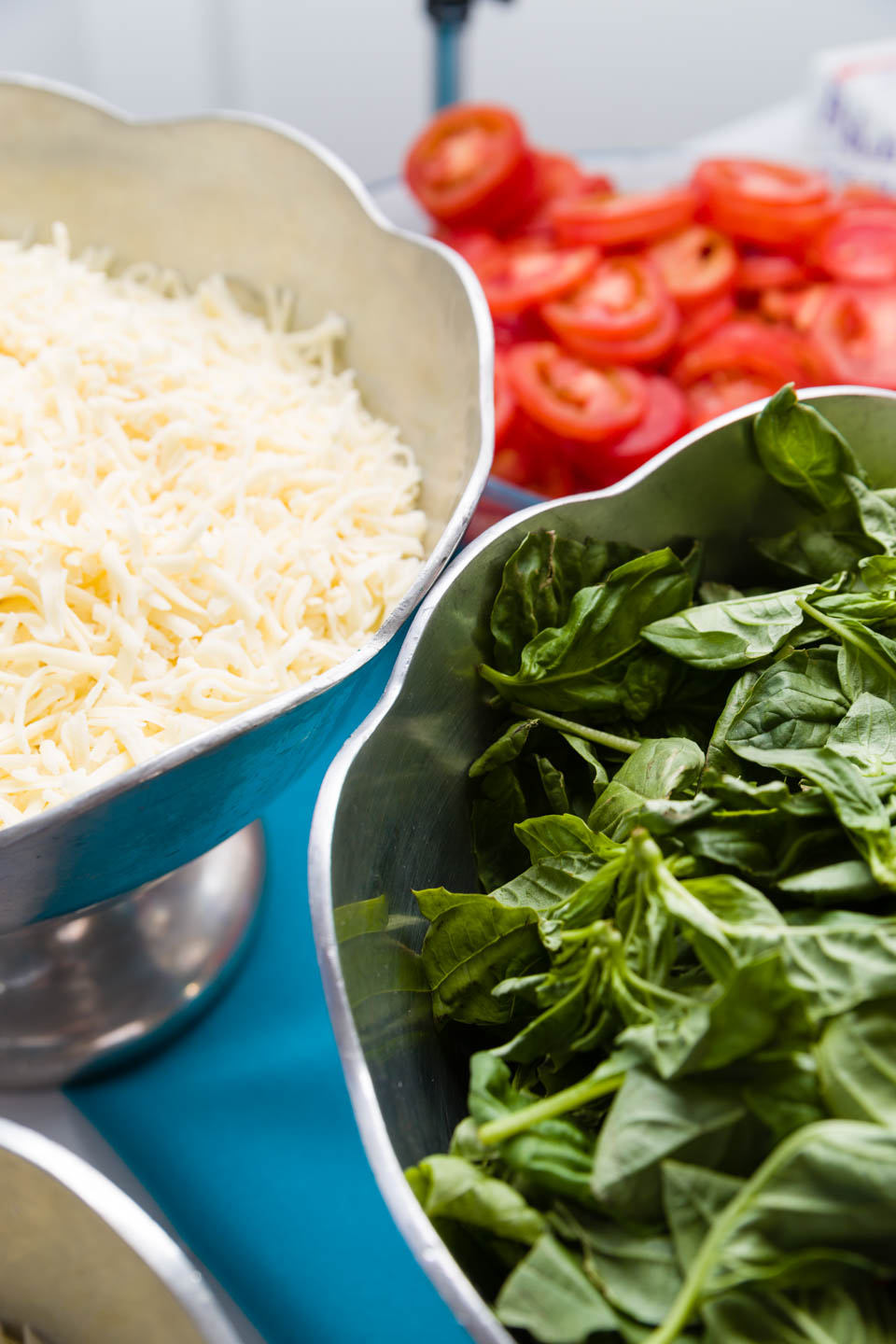 Toppings for margherita pizza... tomatoes, basil, and mozzarella