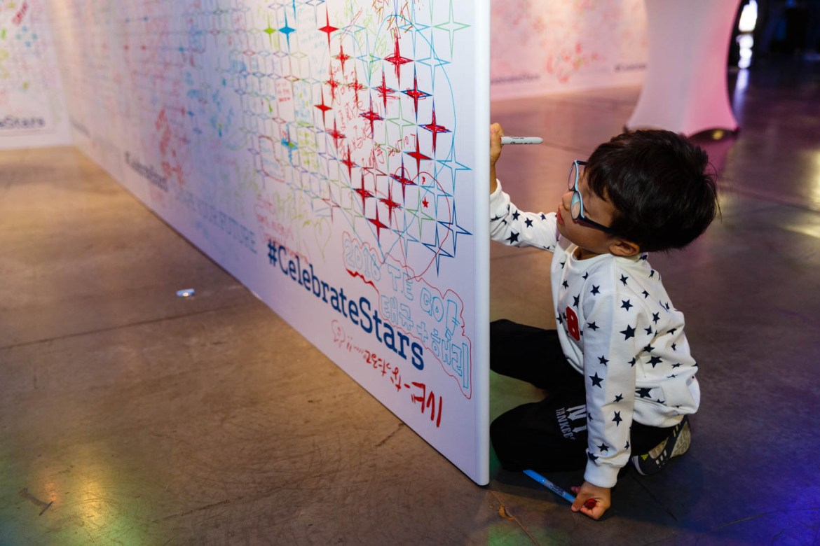 A young participate autographs the wall
