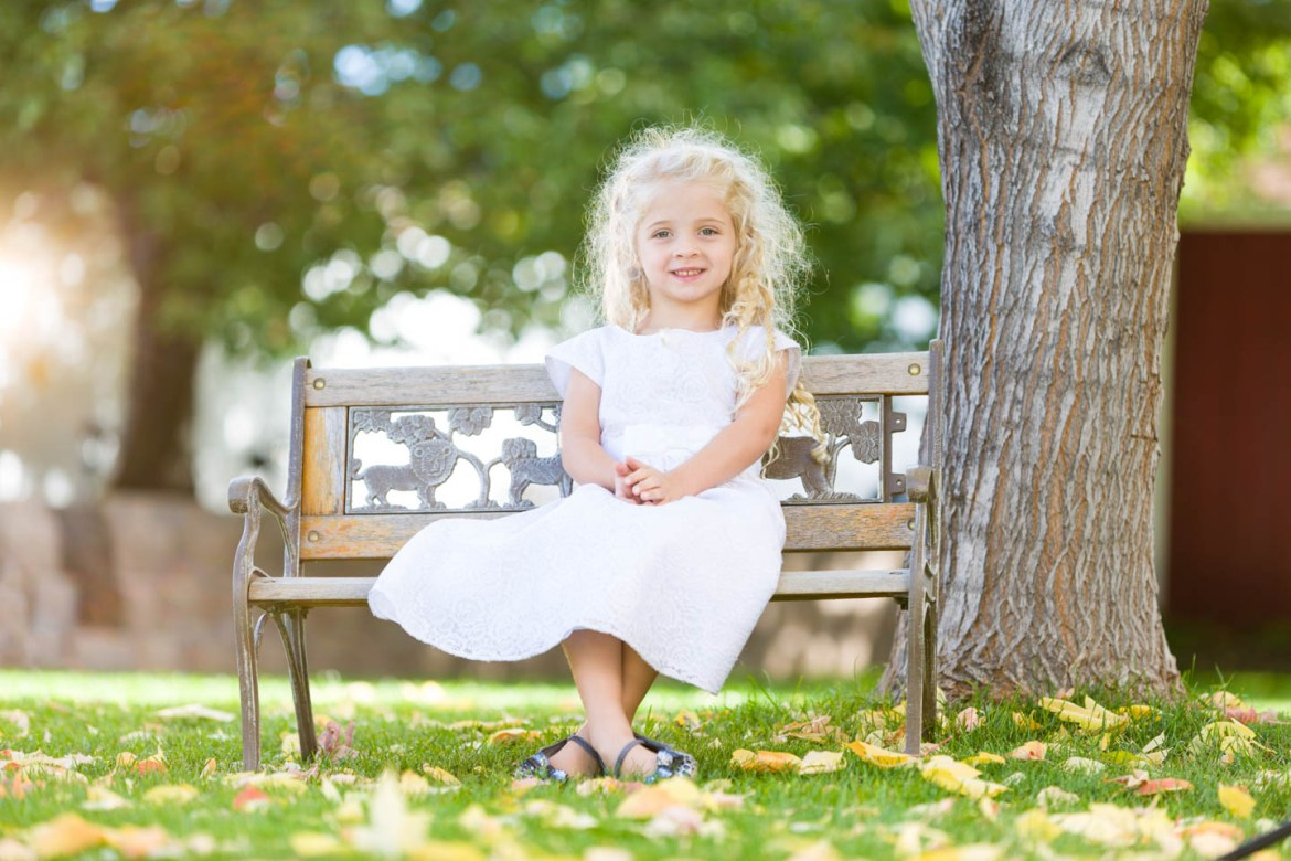 Eve sits on a garden bench surrounded by autumn leaves